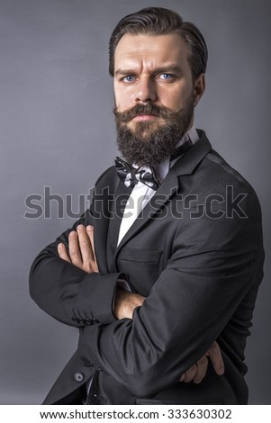 Portrait of an elegant young fashion man with retro look and arms folded over gray background - stock photo