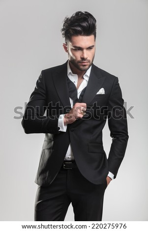 Portrait of an elegant young man in tuxedo looking down while ajusting his tuxedo, holding one hand in his pocket. On grey background. - stock photo