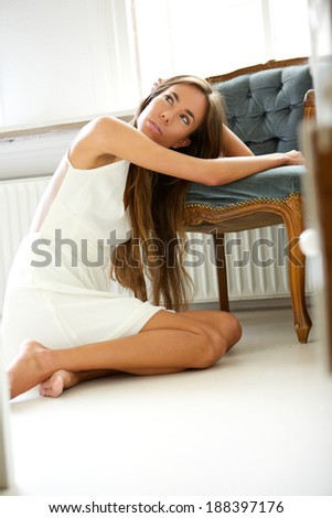 Portrait of an elegant young woman resting on chair