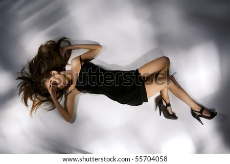 Portrait of an elegantly beautiful young woman in black dress posing on the floor - stock photo