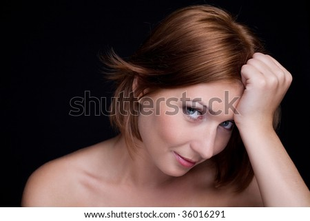 Portrait of an embarrassed woman over black background