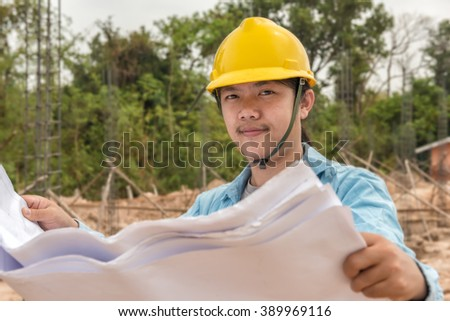 Portrait of an engineer with hard hat holding blue print paper at work - stock photo