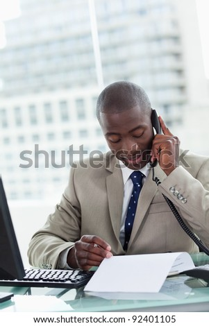 Portrait of an entrepreneur making a phone call while reading a document in his office - stock photo