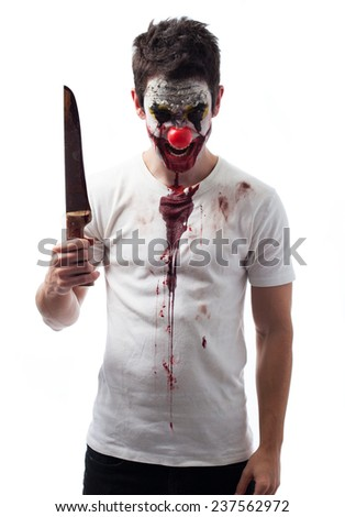 Portrait of an evil clown holding a knife over white background - stock photo