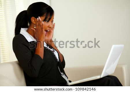 Portrait of an excited executive young woman screaming with hands up while looking to laptop screen and reading amazing great news about a corporate business - stock photo