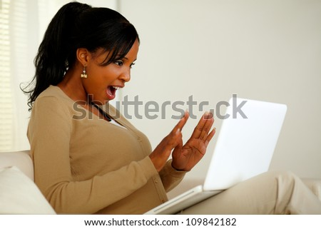 Portrait of an excited woman looking to laptop screen while sitting on sofa at home indoor - stock photo