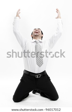 Portrait of an excited young man celebrating success with raised hand against white background - stock photo