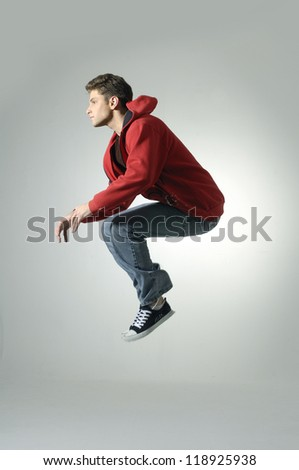 Portrait of an excited young man jumping in air against light background