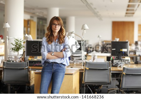 Portrait of an executive professional mature businesswoman sitting on office desk in casual and smiling. Shallow focus. - stock photo