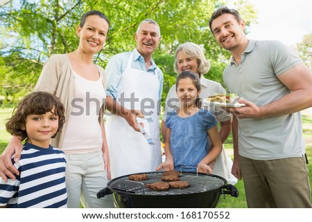 Portrait of an extended family standing at barbecuing in the park - stock photo