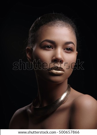 Portrait of an extraordinary beautiful naked african american model with perfect smooth glowing mulatto skin, make up, full golden lips, shaved haircut and gold jewelry on her neck, dark background
