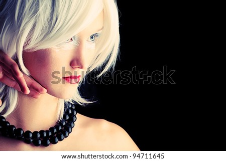 Portrait of an extravagant blonde model over black background. - stock photo