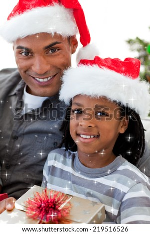 Portrait of an father and son holding a Christmas gift with twinkling stars - stock photo