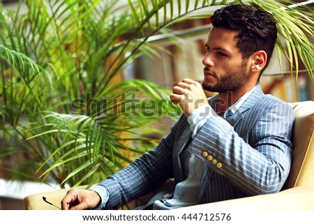 Portrait of an handsome businessman relaxing in garden - stock photo