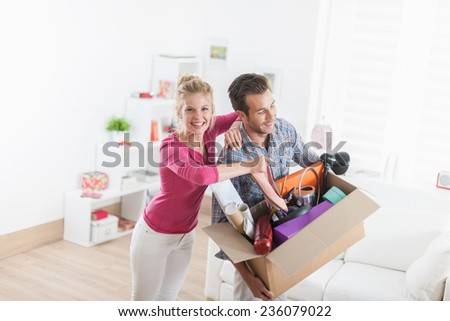portrait of an handsome couple moving in  a new apartment and carrying a box with various objects - stock photo