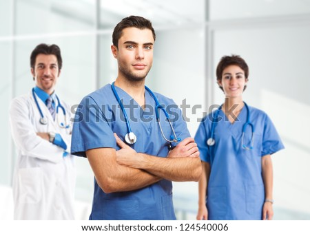 Portrait of an handsome doctor in front of his medical team - stock photo