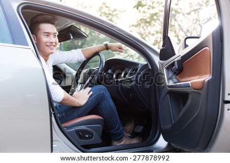 Portrait of an handsome smiling asian business man driving his car with white shirt