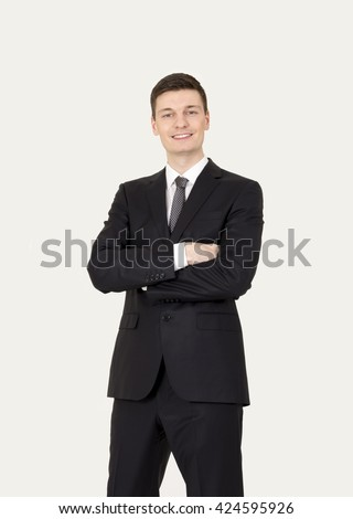 Portrait of an handsome young businessman on the gray background. - stock photo