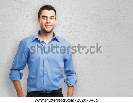 Portrait of an handsome young man leaning against a wall - stock photo