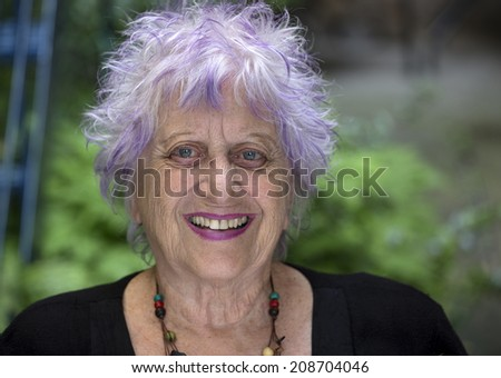 portrait of an happy and colorful old woman - stock photo