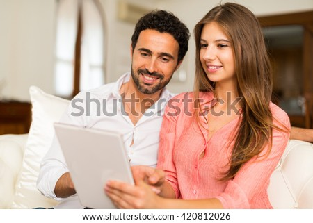 Portrait of an happy couple using a tablet. Shallow depth of field, focus on the woman