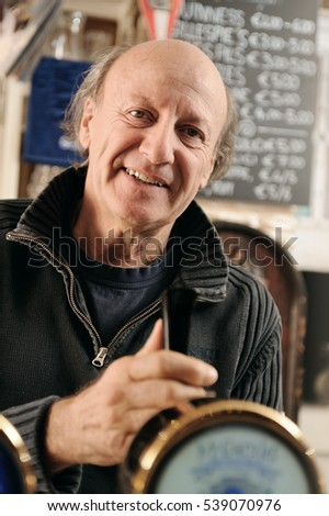 Portrait of an happy man working in a pub