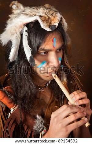 Portrait of an Indian in traditional costume wearing eagle feathers, coyote fur and beads - stock photo