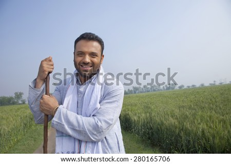 Portrait of an Indian man looking away while holding a stick - stock photo
