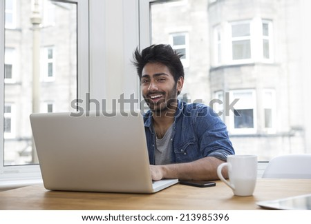 Portrait of an Indian man sitting at a table at home working on a laptop computer. - stock photo