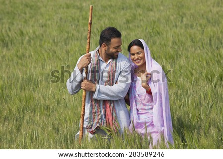 Portrait of an Indian woman standing with her husband in wheat field