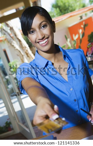 Portrait of an Indian woman using credit card - stock photo