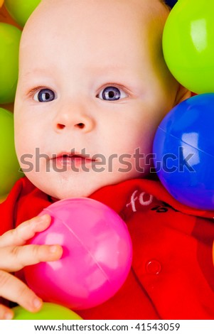 Portrait of an infant lying with many colorful balls - stock photo