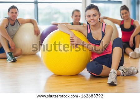 Portrait of an instructor and fitness class with exercise balls at a bright gym - stock photo