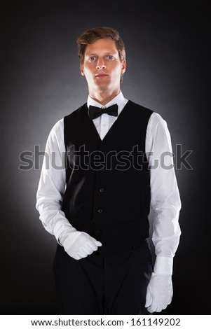 Portrait Of An Male Waiter Standing Over Black Background - stock photo