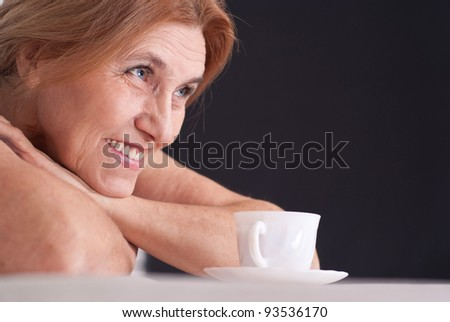 portrait of an old lady with a cup - stock photo