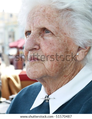 portrait of an old lady with wrinkles and sun stained skin and white hair - stock photo