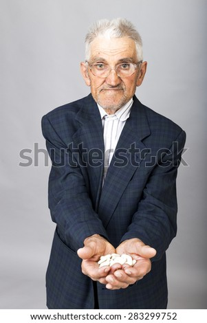 Portrait of an old man with glasses holding a lot of pills in his wrinkled hands over gray background