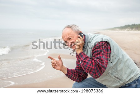 Portrait of an old senior man with a telephone on sea background - stock photo