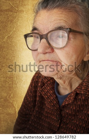 Portrait of an old woman on a vintage background. Dreaming the past - stock photo