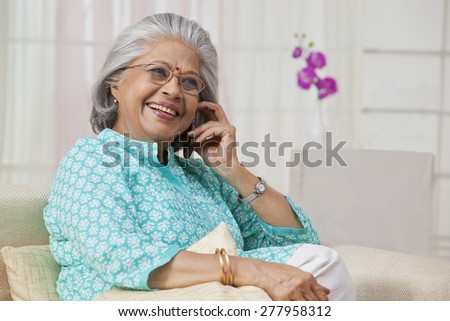 Portrait of an old woman talking on mobile phone - stock photo