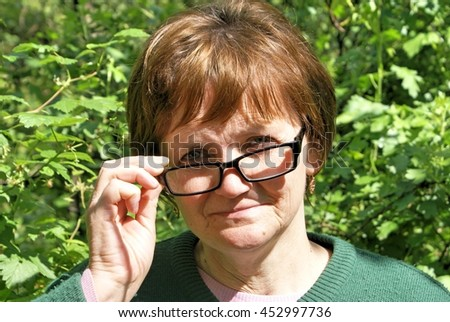 Portrait of an old woman with glasses - stock photo