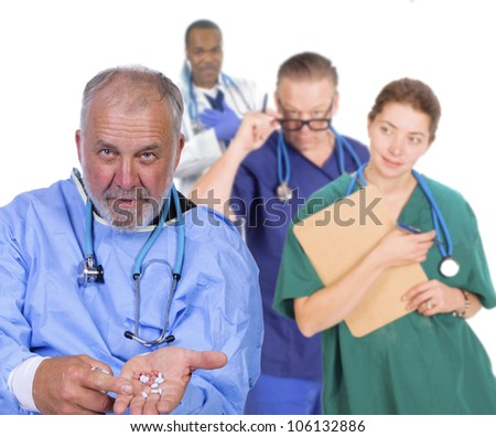 Portrait of an older doctor holding his hand out with pills, standing in front of his team smiling - stock photo