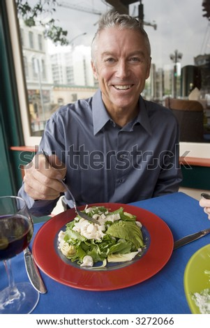 Portrait of an older man eating a salad - stock photo
