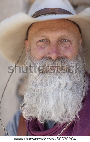 Portrait of an older man with a long white beard and cowboy hat smiling towards the camera. Vertical shot. - stock photo