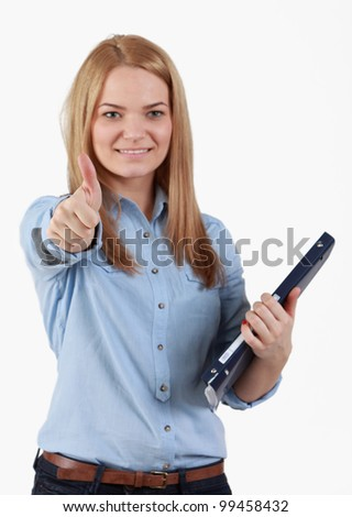 Portrait of an optimistic student blonde girl with her right thumb up and holding a folder in her left hand.The focus is selective on her thumb. - stock photo
