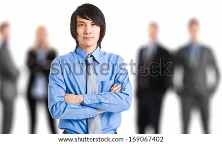 Portrait of an oriental businessman in front of his working team - stock photo