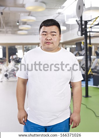 portrait of an overweight young man in fitness center. - stock photo