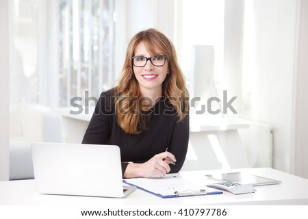 Portrait of an professional investment advisor businesswoman sitting in front of laptop at her desk in an office while looking at camera and smiling.  - stock photo