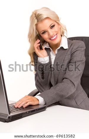 Portrait of an sexy business woman sitting by a desk and laptop speaking over the phone , smiling - stock photo
