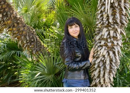 portrait of an ukrainian girl visiting Rome posing near a palm tree - stock photo